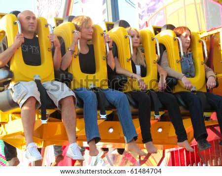 DUSSELDORF, GERMANY - JULY 24: Visitors on Thrill Ride at Kirmes on July 24, 2010 in Dusseldorf, Germany. Kirmes is the biggest summer fair on the north Rhein in Germany. - stock photo