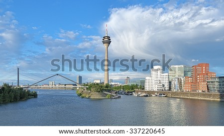 DUSSELDORF, GERMANY - MAY 19, 2015: Media Harbor on the background of cloud front. The photo shows the Rheinturm TV tower with height of 240.5m and the Neuer Zollhof buildings by architect Frank Gehry - stock photo