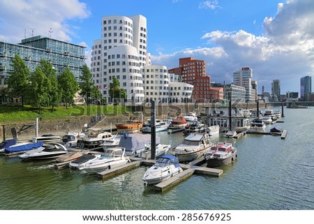DUSSELDORF, GERMANY - MAY 19, 2015: Media Harbor with buildings of Neuer Zollhof. The Neuer Zollhof buldings was designed by the famous American architect Frank O. Gehry and completed in 1998. - stock photo