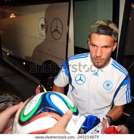 DUSSELDORF, GERMANY - SEPTEMBER 4, 2014: World Cup Champion Lukas Podolski gives autographs on a football on September 4, 2014 in Dusseldorf. - stock photo