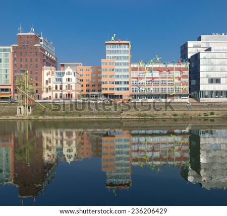 DUSSELDORF - SEPTEMBER 6, 2014: Reflection of office buildings in the media harbor. The Hafen district contains some spectacular post-modern architecture, but also some bars, restaurants and pubs - stock photo