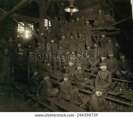 Dust covered Breaker Boys during a noon hour break at a South Pittston Pennsylvania Coal mine. The youngest coal mine workers started at this unskilled work. January 1911 photo by Lewis Hine. - stock photo