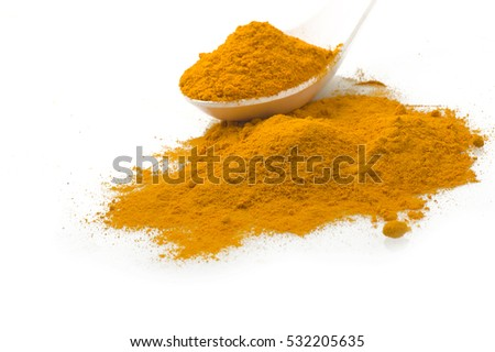 dust of ground turmeric on the spoon