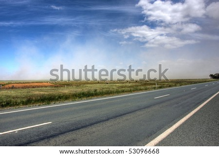 dust storm over an australian road - stock photo