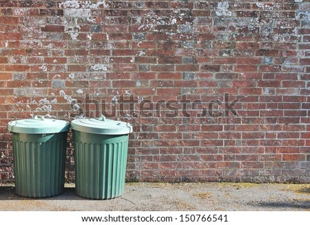 dustbins outside against brick wall - stock photo