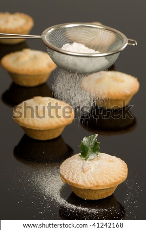 Dusting Christmas mince pies with icing sugar on black background - stock photo