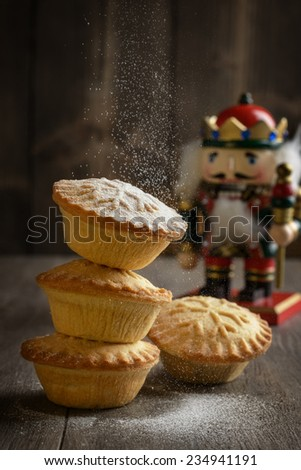 Dusting mince pies with icing sugar for Christmas - stock photo