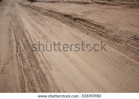 Dusty and rutted dirt road. Focus on tire ruts. - stock photo