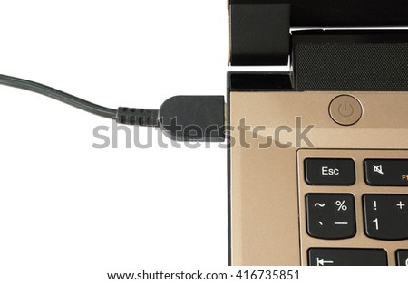 Dusty brown laptop plugged into charging wire adapter on white background - stock photo