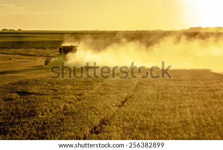 dusty combine on the left with dust cloud moving to the right. yellow sunset during wheat harvest - stock photo
