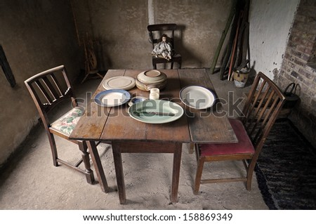 Dusty dinner table in a poor farm workers cottage - stock photo