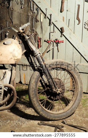 Dusty old motorcycle in garage workshop with the wooden wall background with tools, vertical picture - stock photo
