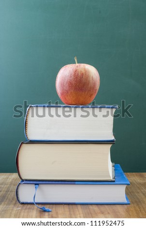 Dusty school books on a desk. On the top an apple and space for text and graphics. - stock photo