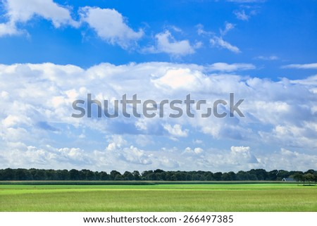 Dutch agrarian landscape with dramatic shaped white clouds in a blue sky. - stock photo