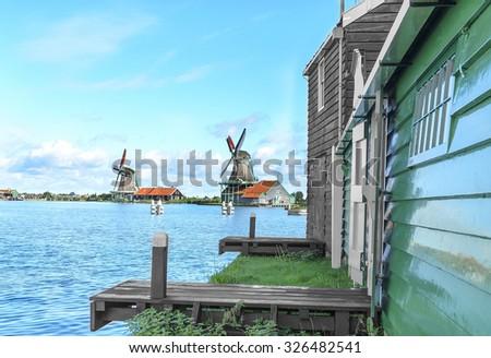 Dutch ancient windmills on the lake shore. - stock photo