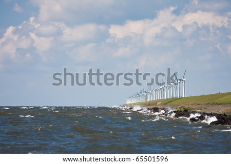 Dutch breakwater with windmills during a heavy storm - stock photo