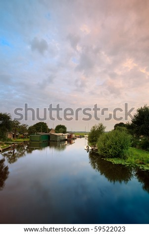 Dutch canal with trees and houses at sunrise - stock photo