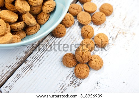Dutch candy pepernoot with bowl on white wooden background - stock photo