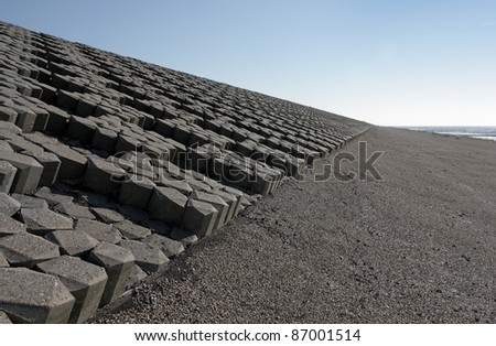 Dutch dike by the North Sea with concrete stones. - stock photo