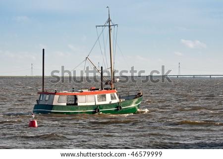 Dutch fishing ship sailing to the sea - stock photo
