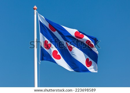 Dutch flag of the province Friesland against a clear blue sky - stock photo