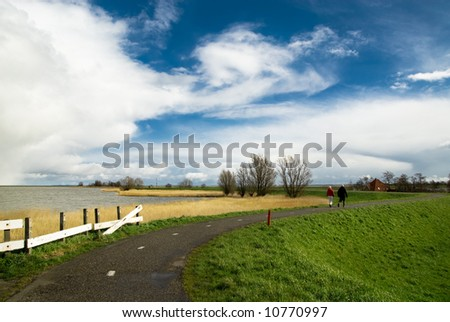 dutch landscape with a couple walking - stock photo