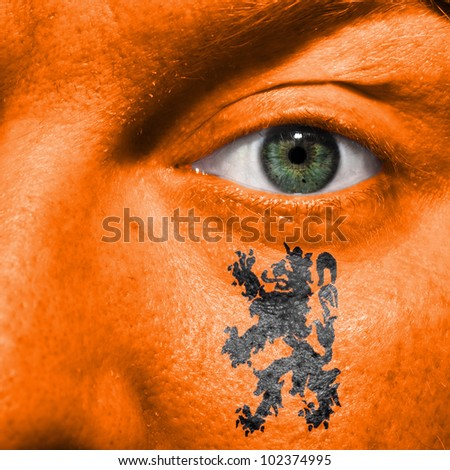 Dutch Lion painted on orange face with green eye to show Netherlands support in sport matches - stock photo