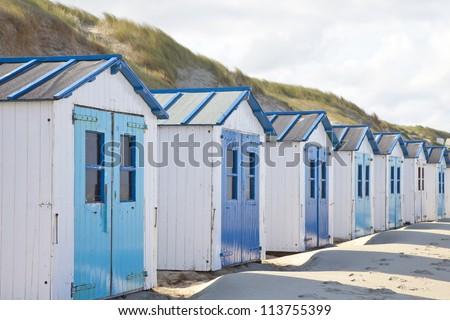 Dutch little houses on beach in De Koog Texel, The Netherlands - stock photo