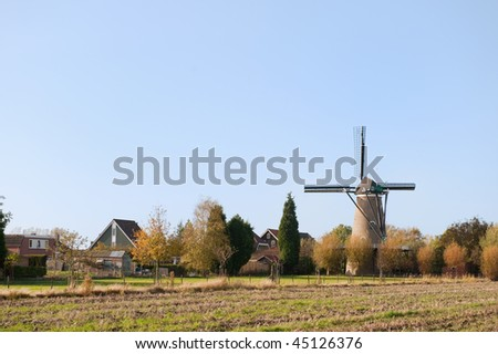 Dutch little village with windmill in landscape