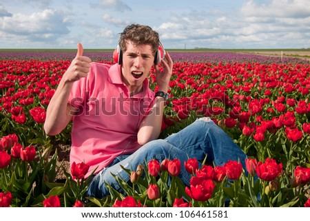 Dutch man sitting in flower fields listening to cool music - stock photo