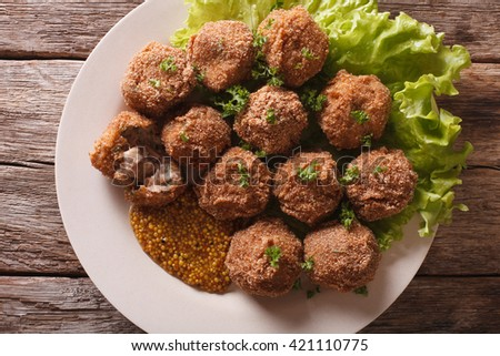 Dutch meat croquettes Bitterballen and mustard close up on a plate on the table. horizontal view from above - stock photo
