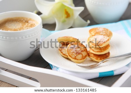 Dutch mini pancakes called poffertjes, sprinkled with powdered sugar - stock photo
