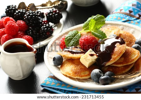 Dutch mini pancakes called poffertjes with berries and chocolate sauce - stock photo