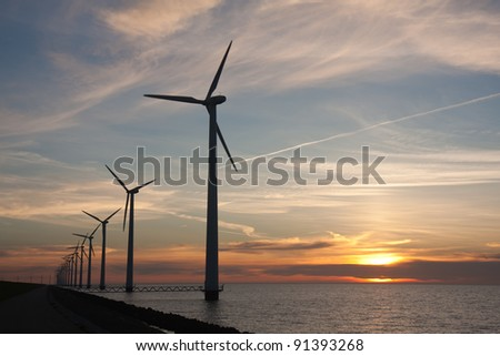 Dutch offshore windturbines during a beautiful sunset - stock photo
