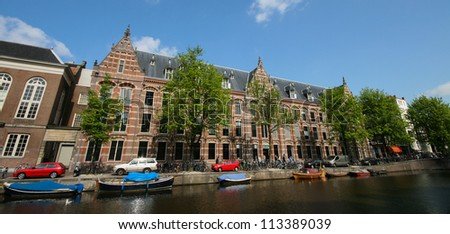Dutch old house along canal in Amsterdam, Netherlands - stock photo