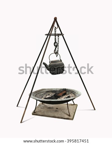 Dutch oven cast iron kettle and rod tripod over firewood metal pan. - stock photo