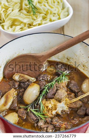 Dutch oven full of Greek Beef Stifado served with egg noodles - stock photo