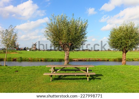 Dutch pastoral green meadow with water canals and windmills landscape. Netherlands  - stock photo