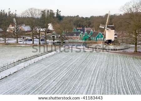 dutch post mill from 1665 with 17th and 18th century houses - stock photo