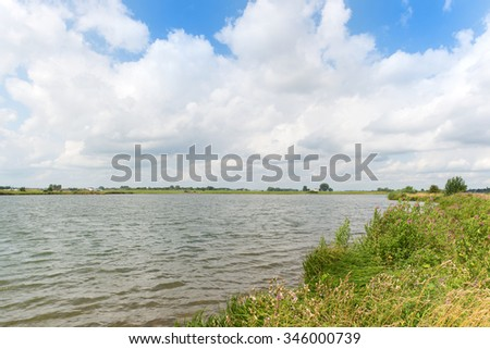 Dutch river Nederrijn with clouds - stock photo