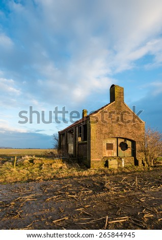 Dutch small pumping station built in 1946 will be demolished to make way for a new one. It is at the end of winter season and twilight is approaching now. - stock photo