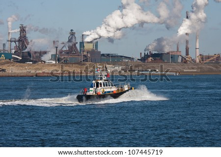 Dutch steel factory along the coast with motorboat in front - stock photo