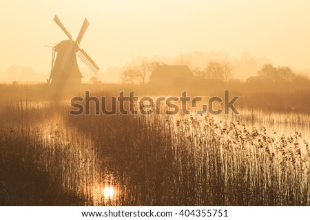 Dutch sunrise with traditional windmill in the wetlands and  spring fog. - stock photo