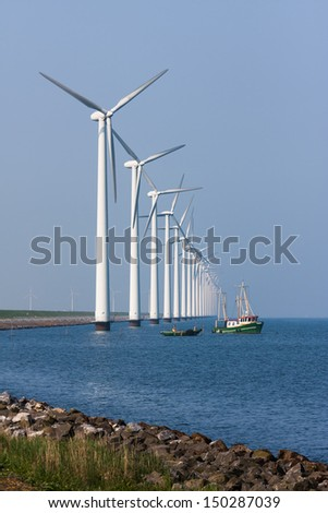 Dutch wind turbines with fishing ship - stock photo