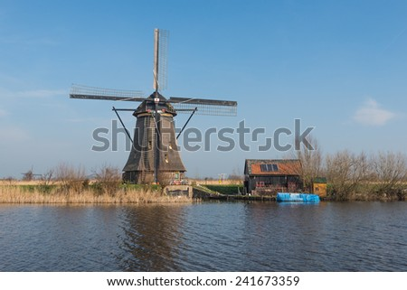 Dutch windmill and a small barn next to a canal on a sunny day in springtime. - stock photo