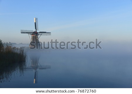 Dutch windmill at a lake in the fog. - stock photo