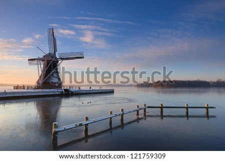 Dutch windmill at a lake on a cold morning in december. - stock photo