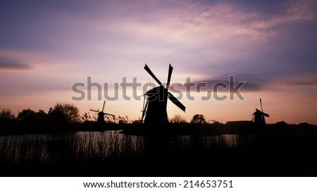 Dutch windmill at sunset at Kinderdijk in Netherlands - stock photo