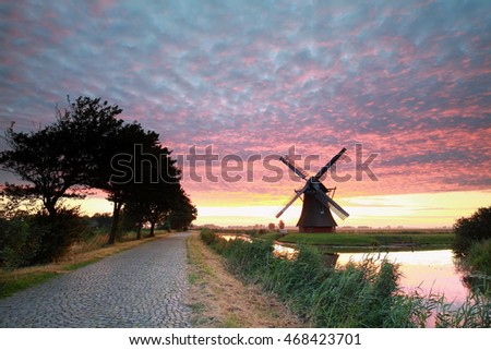 Dutch windmill by road at dramatic sunrise, Groningen, Netherlands