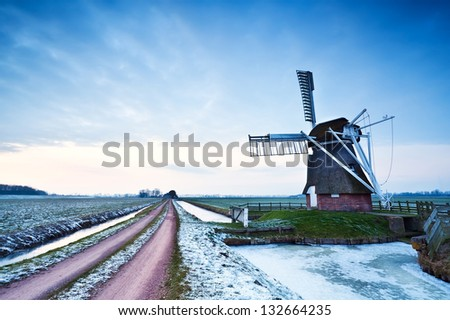 Dutch windmill during winter in dusk - stock photo